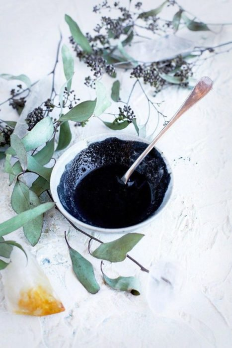 White bowl with green plants around filled with activated charcoal face mask