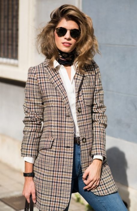 Girl wearing jeans, white blouse and blazer with tartan print in brown tones