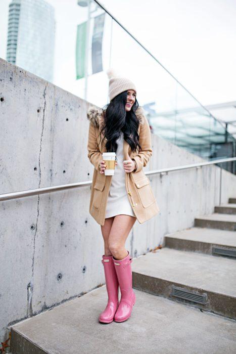 Chica usando unas botas para lluvia en color rosa