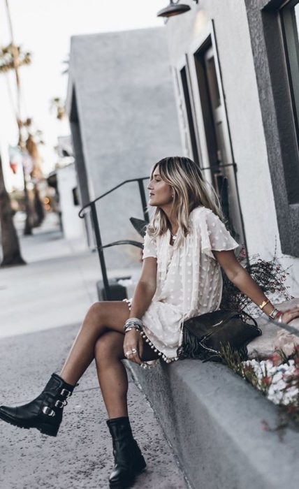 Girl sitting on the street while wearing a white dress with black combat boots