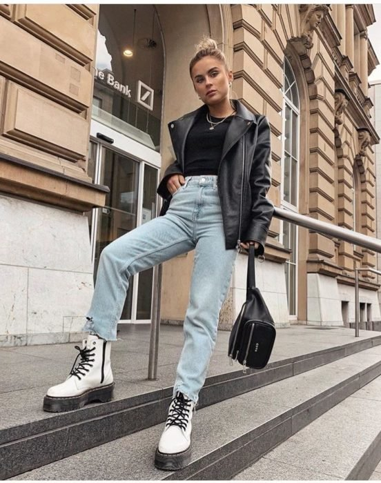 Girl wearing white Dr. Marteen boots with jeans and black jacket