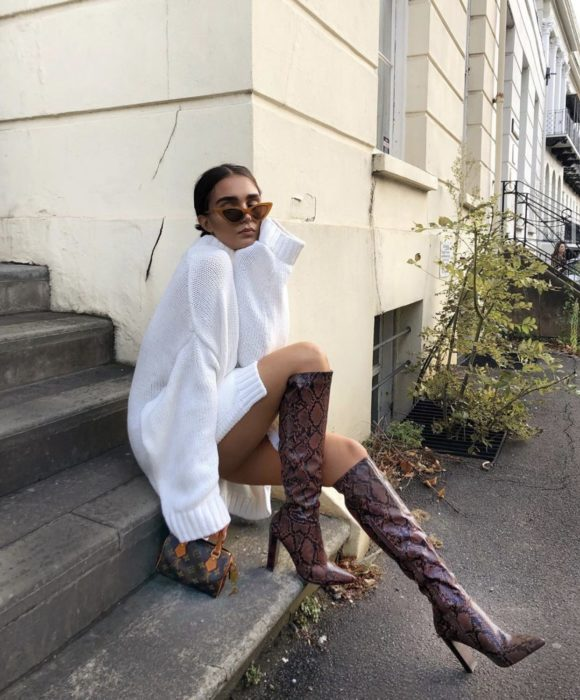 Girl sitting on some stairs posing for a photo while wearing a white outfit with long cherry-colored boots