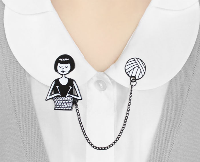Shirt brooch in the shape of a girl knitting
