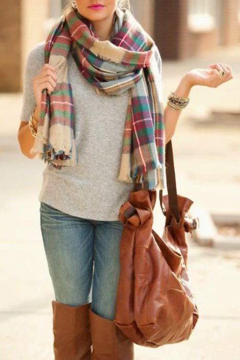 Girl wearing jeans, gray sweater, and plaid scarf, along with a camel-colored handbag