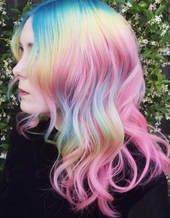 Chica con cabello teñido de colores arcoíris pastel, azul, verde, amarillo, rosa y morado, ondulado