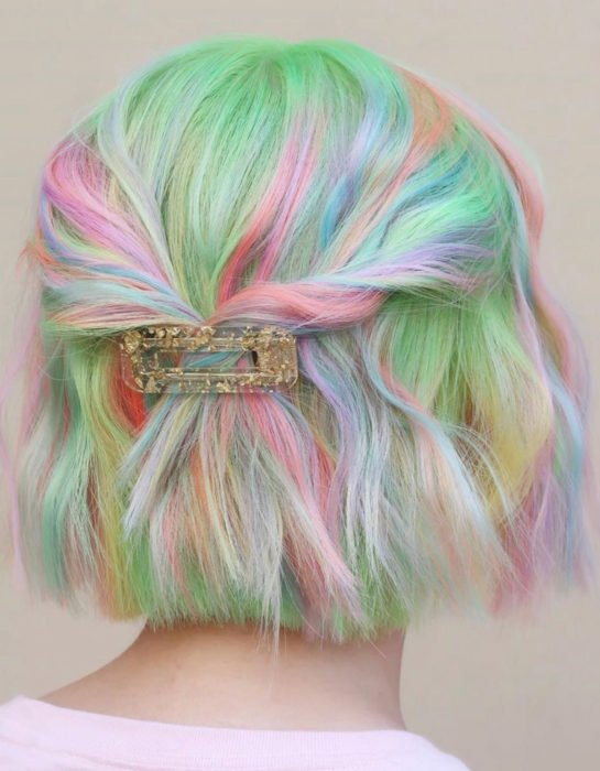 Girl with short hair dyed pastel rainbow colors, blue, green, yellow, pink and purple, hairstyle with clasp