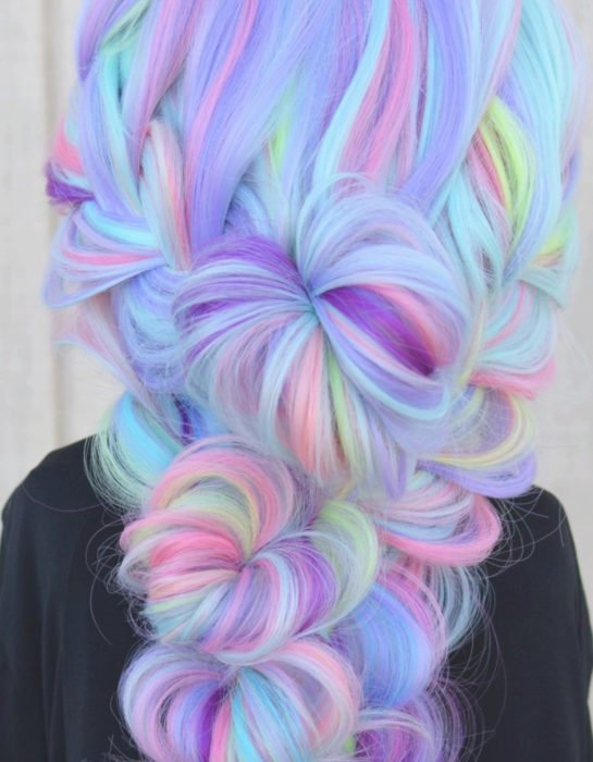 Girl with long hair dyed in pastel rainbow colors, blue, green, yellow, pink and purple, hairstyle with heart buns