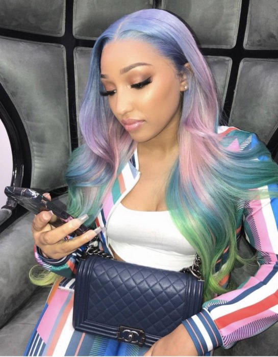 Woman sitting looking at her cell phone, with simple makeup, long, wavy hair dyed in pastel rainbow colors, blue, green, yellow, pink and purple
