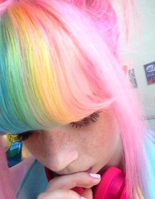 Freckled girl with straight hair with fringe and dyed in pastel rainbow colors, blue, green, yellow, pink and purple