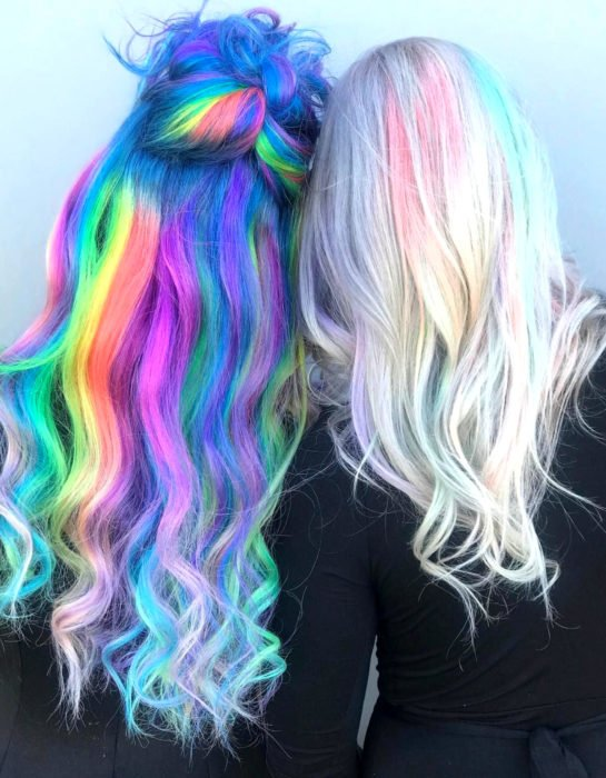 Women, friends with hair dyed in pastel rainbow colors, blue, green, yellow, pink and deep purple and pastel