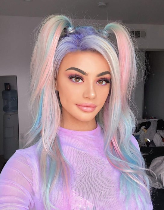 Girl with long, wavy hair dyed in pastel rainbow colors, blue, green, yellow, pink and purple, hairstyle with two ponytails