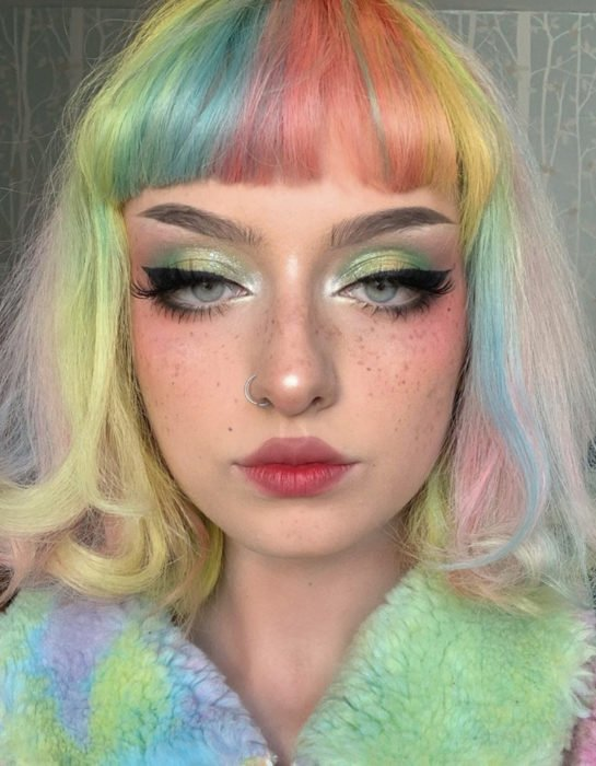 Freckled woman with nose piercing, outlined gray eyes with short hair dyed in pastel rainbow colors, blue, green, yellow, pink and purple, wavy, fringe