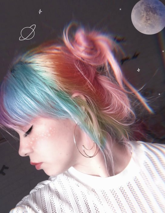 Girl with straight hair dyed in pastel rainbow colors, blue, green, yellow, pink and purple, bun hairstyle and moon earrings