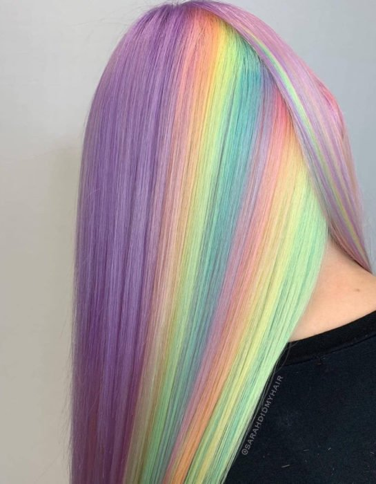 Woman with long straight hair dyed in pastel rainbow colors, blue, green, yellow, pink and purple