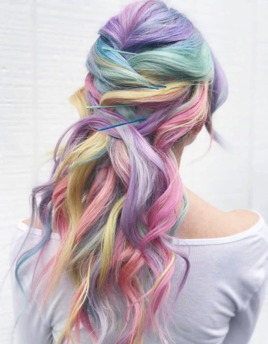 Girl with long wavy hair dyed in pastel rainbows, blue, green, yellow, pink, and purple; Tousled braid hairstyle with statement barrettes