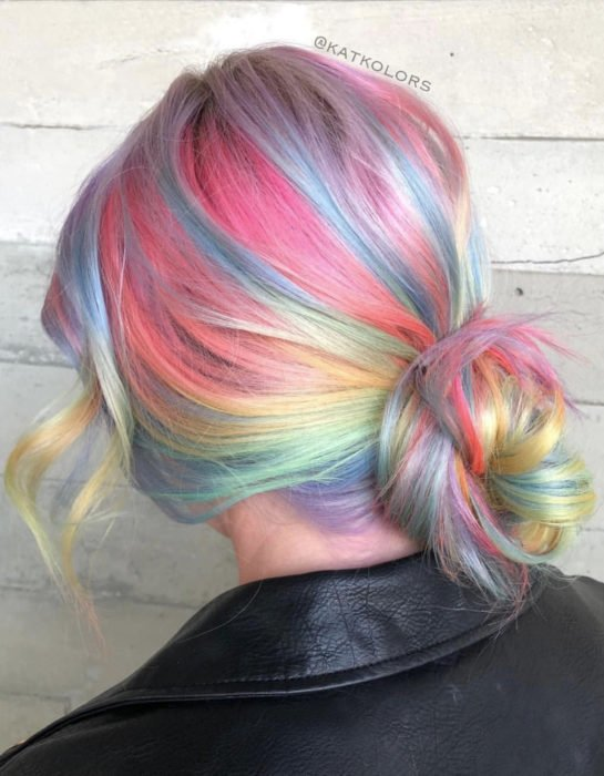 Girl with long straight hair dyed in pastel rainbow colors, blue, green, yellow, pink and purple, tousled bun hairstyle