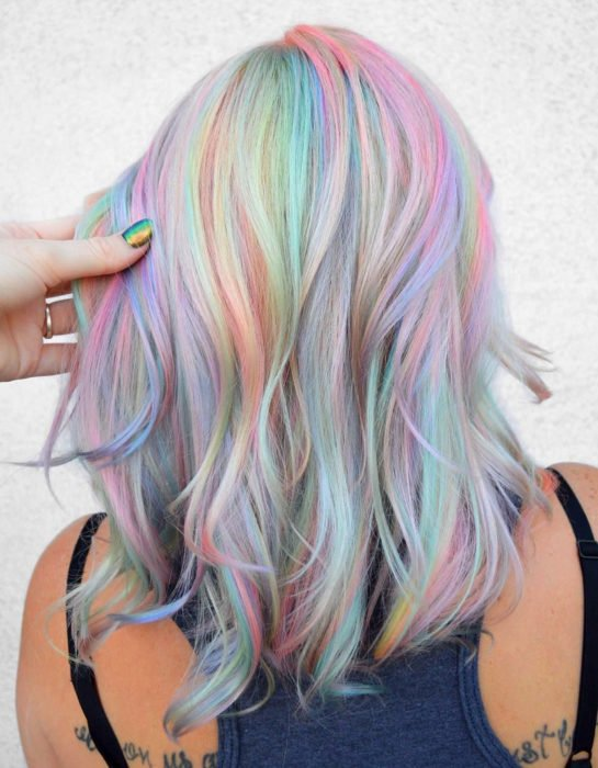 Woman with short wavy hair dyed in pastel rainbow colors, blue, green, yellow, pink and purple