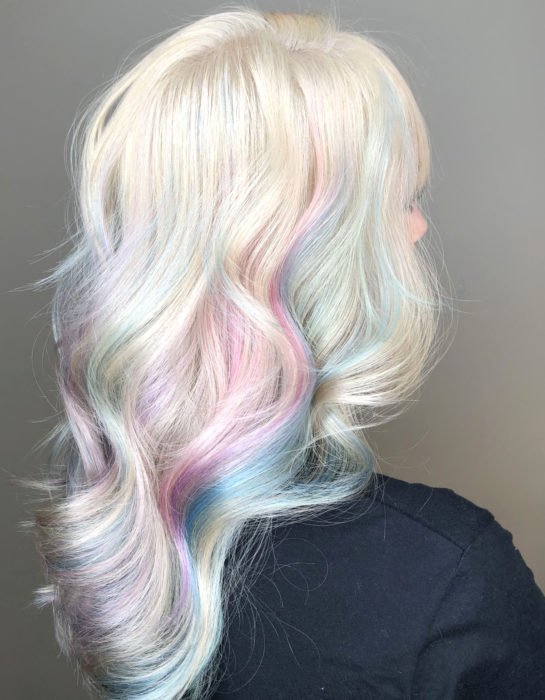 Girl with long, wavy and white hair dyed pastel rainbow colors, blue, green, yellow, pink and purple