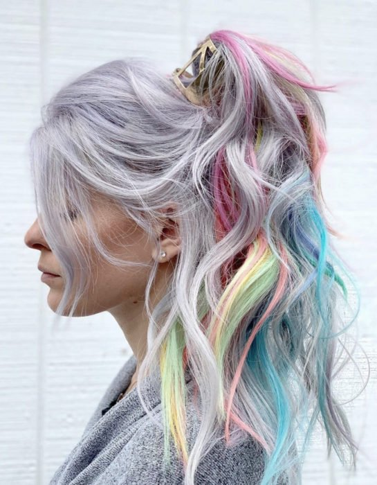 Girl with lavender gray hair, long, wavy and dyed in pastel rainbow colors, blue, green, yellow, pink and purple, tousled ponytail hairstyle