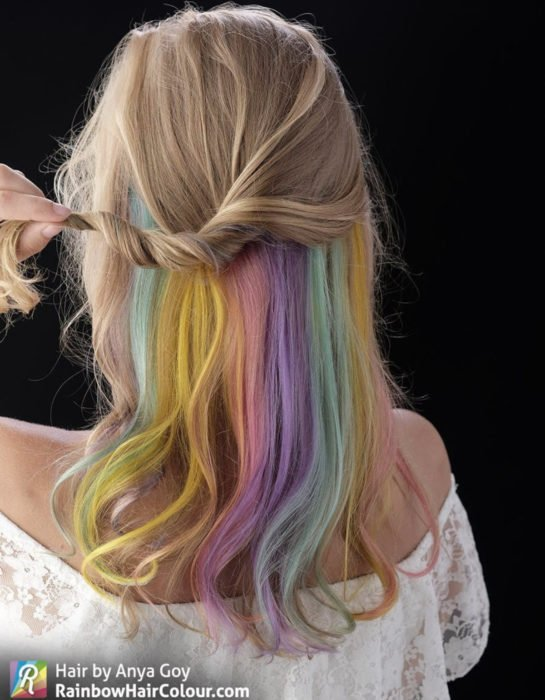 Woman with hair below the shoulders, wavy, ash blonde dyed in half pastel rainbow colors, blue, green, yellow, pink and purple