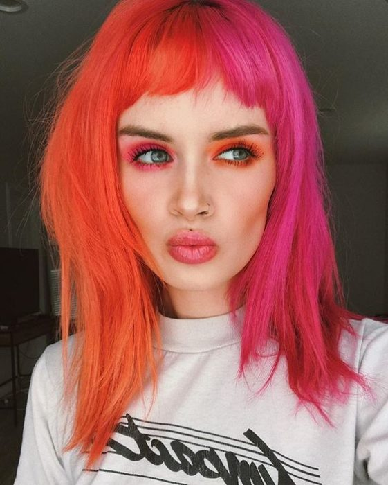 Girl with half fiery orange, half pink hair