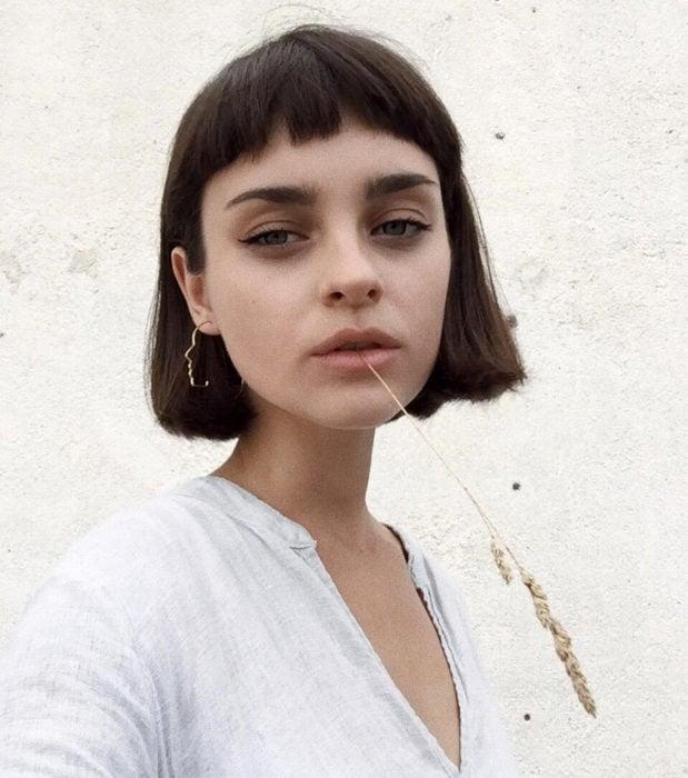 Looks aesthetic con cabello corto color castaño, de hongo, con fleco muy corto, mujer con espiga de trigo en la boca, ojos verdes, maquillaje sencillo