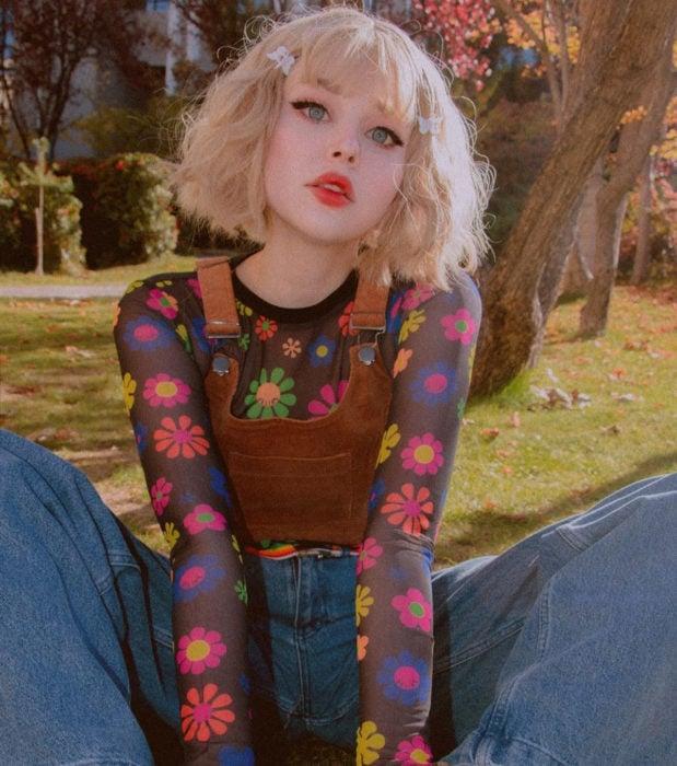Looks aesthetic con cabello corto color rubio, ondulado, con pucas, blusa de flores hippies, overol, chica kawaii sentada en el pasto en el parque