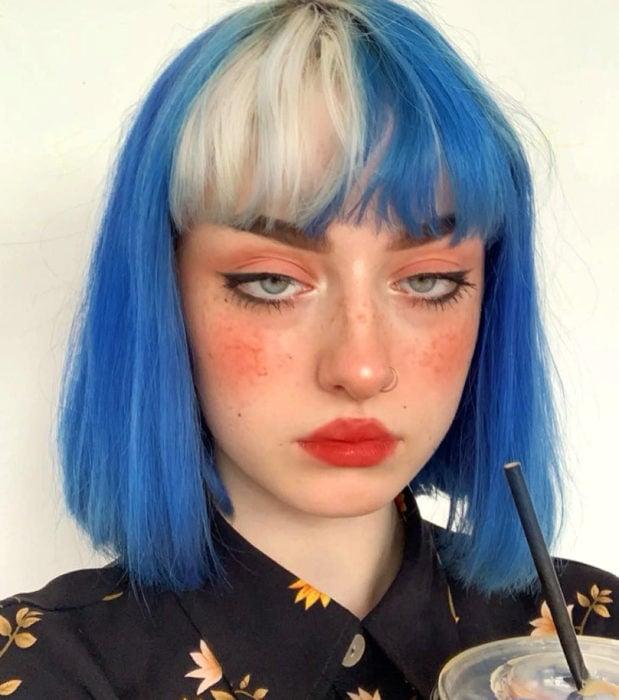 Looks aesthetic con cabello corto color azul y blanco, lacio, con fleco, mujer de ojos verdes, pecas, perforación en la nariz y maquillaje sencillo con mucho blush