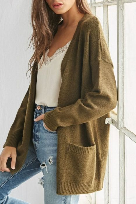 Girl wearing jeans, white blouse and olive green long open cardigan