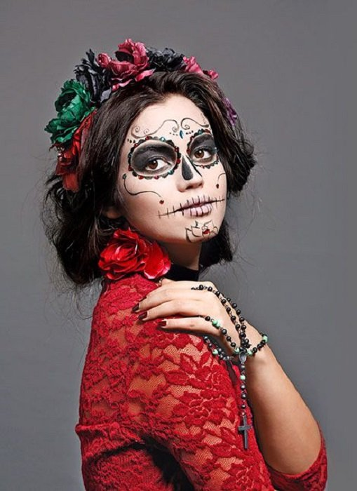 Catrina makeup on full face in black and white tones and hair collected with red and green ribbons