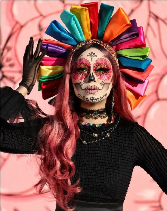 Full face catrina makeup in pink, black and white colors, with a ribbon crown as a traditional Mexican doll