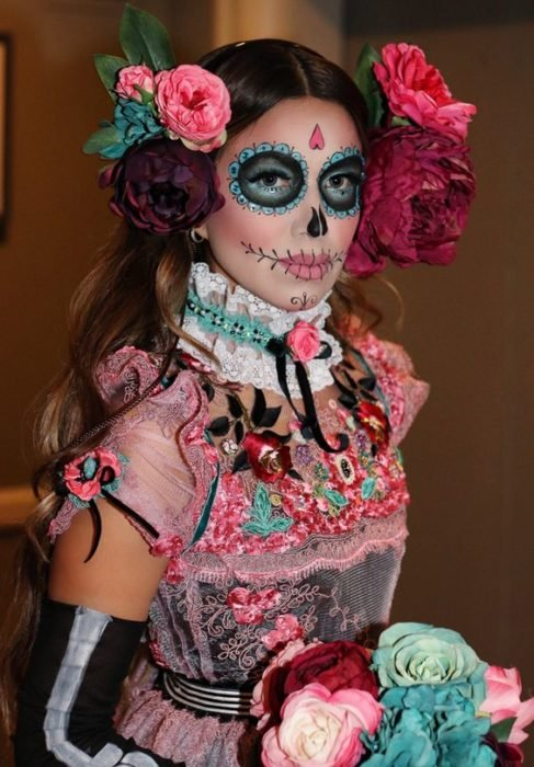 Catrina makeup on full face with aqua tones and giant roses on the head