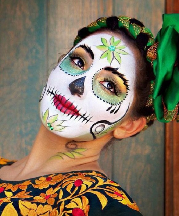 Full-face catrina makeup in green tones and red lips, with Adelitay and green ribbons updo