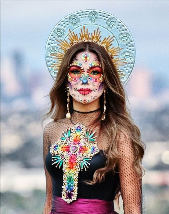 Catrina makeup in vibrant colors and loose hair and saints aura crown