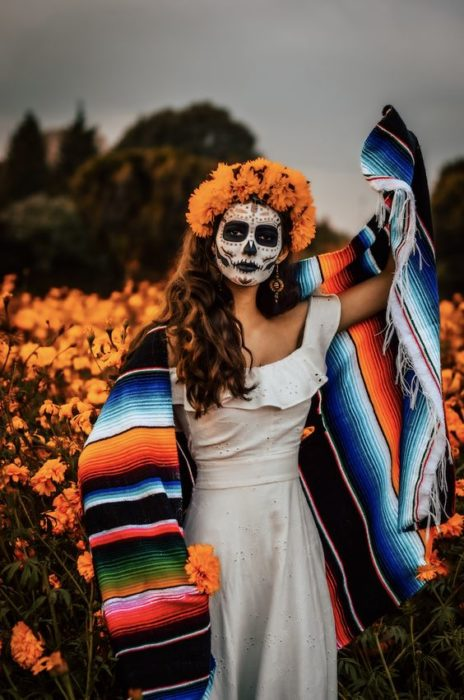 Full face catrina makeup with black details and marigold crown and loose hair