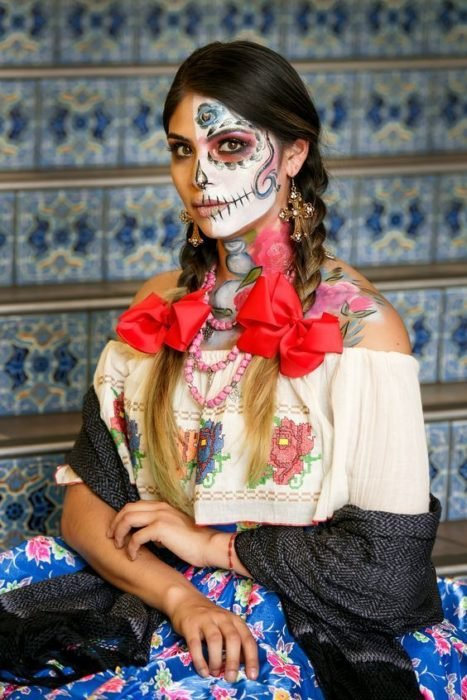 Catrina makeup on half the face, with a hairstyle with two braids on the sides
