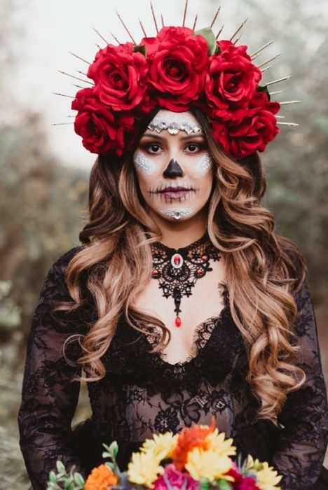 Catrina makeup on a full face, with black and white details and a headdress of red roses on the hair and this loose