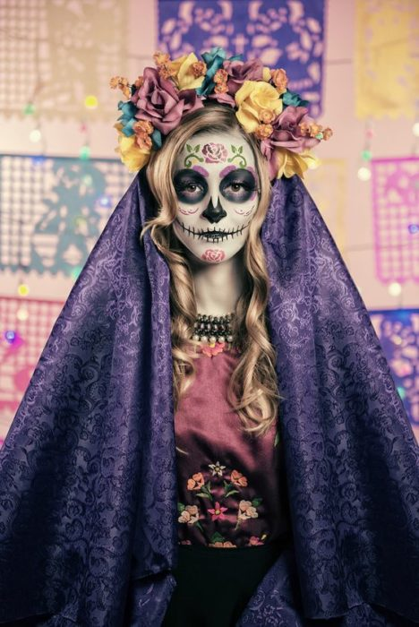 Catrina makeup on full face in white, black, green and pink tones, and headdress of yellow flowers