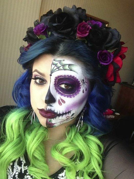 Catrina makeup on half of the face, in black, white and purple colors, with a crown of flowers of the same color