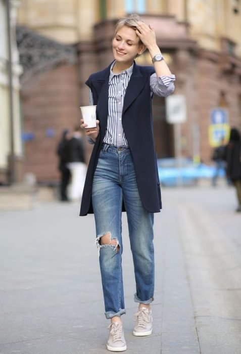 Girl wearing ripped jeans, gray tennis shoes, blue shirt and long navy blue vest