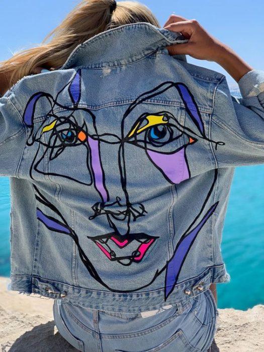 Chaqueta denim customizada con una pintura de un rostro en la parte de la espalda