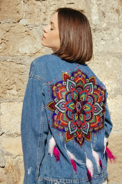 Custom denim jacket with an embroidered mandala on the back and some feathers on the bottom