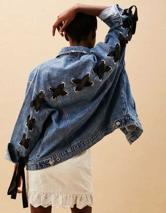 Custom denim jacket with perforations and black lace from sleeves to sleeves across the back