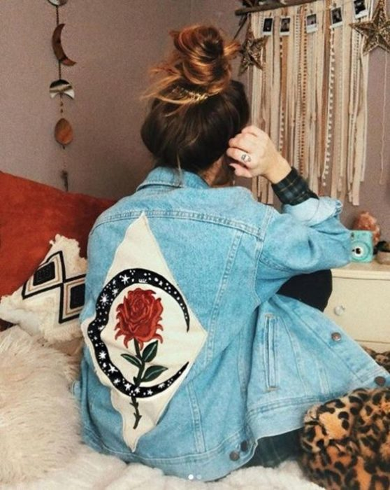 Custom denim jacket with painting of a white diamond and a moon and a rose in the center area