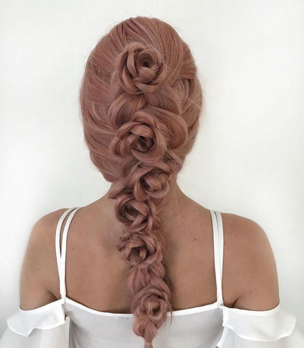 Chica con el cabello trenzado con diferentes rosas en forma de una cascada