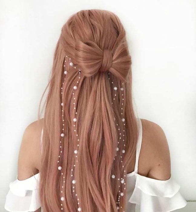 Chica con el cabello trenzado en forma de moño con decoraciones de perlas
