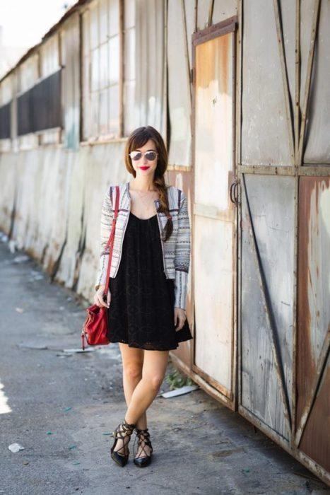 Chica con vestido negro, saco blanco con rayas negras y flats negros con cintas de bailarina