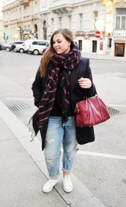 Chuca curvy con saco negro, bufanda negra con rayas rojas, jeans claros y converse blancos