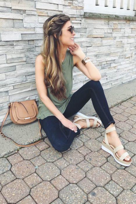 Chica sentada con blusa sin mangas color verde militar, jeans y sandalias claras