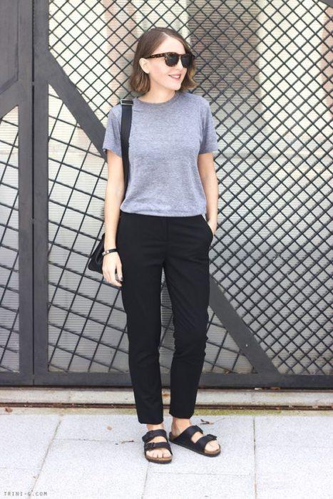 Chica con cabello corto castaño, pantalón negro, blusa gris y sandalias negras